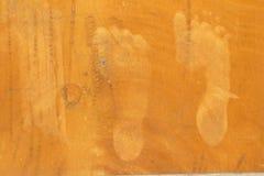 Voetdrukken op de oranje muur stock afbeeldingen