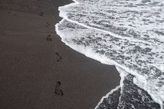 Voetdrukken op zwart zand royalty-vrije stock afbeelding