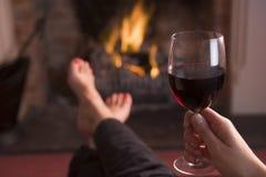Voeten die bij open haard met wijn verwarmen royalty-vrije stock afbeeldingen
