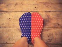 Voeten die blauwe en rode sokken met witte stervorm dragen op houten Stock Afbeelding