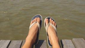 Voeten die Blauwe Stof Flip Flops op Houten Dok dragen - Zitting in de Zon royalty-vrije stock afbeelding