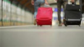 Voeten die op de platformpassagiers lopen met een koffer, jong paar die langs het platform aan de trein lopen met