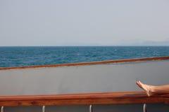 Voeten die op een zeilboot met oceaanachtergrond ontspannen Royalty-vrije Stock Afbeeldingen