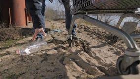 Voeten die van de close-up de dakloze mens plastic fles nemen stock footage