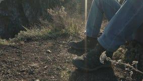 Voeten die van de mens de toerist van de de reizigerswandelaar van trekkingsschoenen de dragen zitten op een backlit rots stock videobeelden