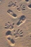 Voeten en handen op het strand Stock Fotografie