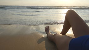 Voeten het sexy meisje liggen op het strand Oceaangolven die over gelooid vrouwelijk benen en lichaam wassen Mooie Jonge Vrouw stock fotografie