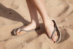 Voeten in het zand met wipschakelaars stock foto's