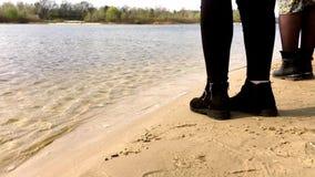 Voeten meisjes die zich in laarzen en broeken op het strand dichtbij het water bevinden stock videobeelden