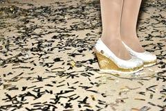 Voeten meisjes in witte schoenen en kousen en confettien op de vloer Stock Foto's