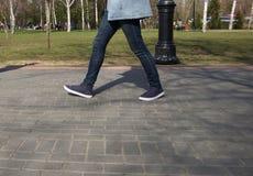 Voeten mensen die in sportenschoenen lopen onderaan de straat op een zonnige dag stock afbeeldingen