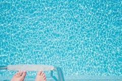 Voeten ongeveer onderaan ladder in een fonkelende pool te beklimmen Royalty-vrije Stock Fotografie
