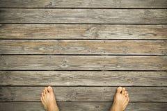 voeten op een hardhoutvloer Stock Afbeeldingen