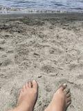 Voeten op een zandig strand in de zomer Stock Foto's