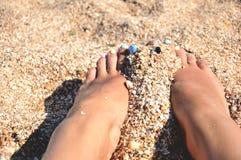 Voeten op het strand worden geschuurd dat Stock Foto