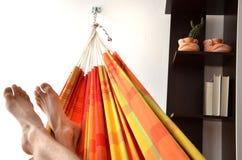 Voeten van de mens die in heldere hangmat binnen de vlakte ligt Royalty-vrije Stock Foto