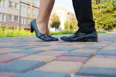 Voeten van de mens en vrouw terwijl het kussen op een romantische vergadering Royalty-vrije Stock Afbeelding