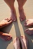 Voeten van een familie in het fijne zand van het strand Royalty-vrije Stock Afbeeldingen