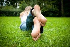 Voeten van een jonge vrouw die in het gras ligt Stock Fotografie