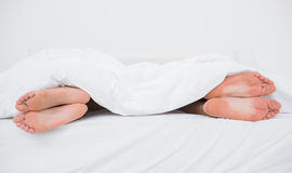 Voeten van een paar op hun overkanten in bed Royalty-vrije Stock Afbeeldingen