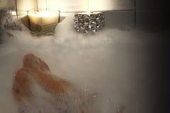 Voeten van een vrouw in het schuimbad, vrouw het ontspannen in badkuip, het besteden vreedzame tijd thuis royalty-vrije stock foto