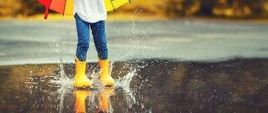 Voeten van kind in gele rubberlaarzen die over vulklei in Ra springen stock afbeeldingen