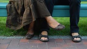 Voeten van man en vrouwenzitting op bank stock videobeelden