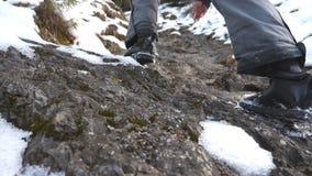 Voeten van onherkenbare kerel die omhoog op sleep van heuvel bij ochtend beklimmen Jonge mannelijke toerist die op sneeuwberg lop stock videobeelden