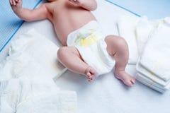 Voeten van pasgeboren baby op veranderende lijst met luiers Royalty-vrije Stock Foto