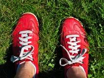 Voeten van persoon in rode tennisschoenen Stock Fotografie