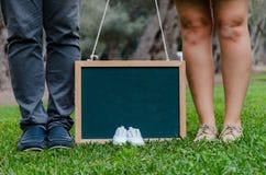 Voeten van vader en moeder met babyschoenen en een zwarte lei royalty-vrije stock fotografie