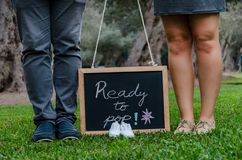 Voeten van vader en moeder met babyschoenen en een zwarte lei royalty-vrije stock foto