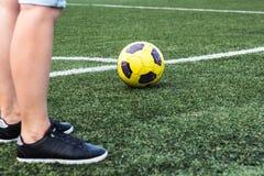 Voeten van vrouw in tennisschoenen en voetbalbal royalty-vrije stock afbeelding