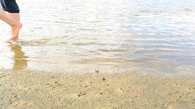 Voeten vrouw het lopen op de kust stock footage