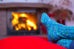 Voeten in wollen blauwe sokken door de open haard royalty-vrije stock foto