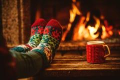 Voeten in wollen sokken door de Kerstmisopen haard De vrouw ontspant royalty-vrije stock foto