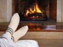 Voeten in wollen sokken en gebreide plaid voor de open haard Sluit omhoog op voeten Het comfortabele ontspannen magische binnenla stock foto