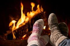 Voeten in wolsokken die bij de open haard verwarmen Stock Afbeeldingen