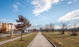 Voetgang of stoepbestrating met park aan de ene kant en stedelijk verkeersweg op andere in de stadsstraat met blauw stock foto