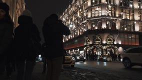 Voetgangers die de straat van de nachtstad, lopen die de bouw met opvlammend licht filmen stock video
