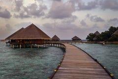Voetgangersbrug die tot houten bungalowwen over het overzees leiden stock foto