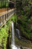 Voetgangersbrug over een waterval. Stock Afbeeldingen