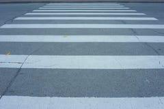 Voetgangersoversteekplaats, barsten op asfalt, twee gele bladeren stock foto's