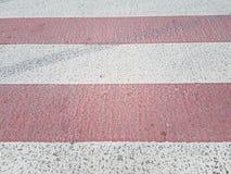 Voetgangersoversteekplaats op de weg, afwisselende strepen van een verf rode en witte, stedelijke achtergrond Stock Fotografie