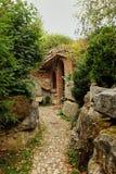 Voetpad door een tuin die tot de ingang van een Middeleeuws Engels Huis rond de klip, rode baksteenvoordeur leiden royalty-vrije stock foto