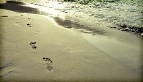 Voetstappen in het zand bij het strand royalty-vrije stock foto's