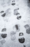 Voetstappen in natte sneeuw op asfaltweg Royalty-vrije Stock Afbeelding