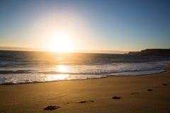 Voetstappen op een strand bij zonsondergang Stock Fotografie