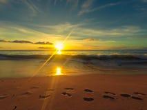 Voetstappen op het strand met een warme zonsondergang Stock Fotografie