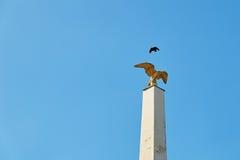 Vogel fliegt über einen vergoldeten Adler auf einer Spalte am Haupttor des Schonbrunn-Palastes in Wien Lizenzfreies Stockbild